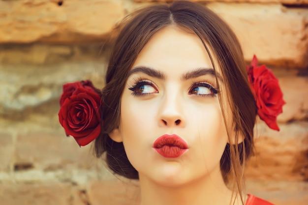 호기심 많은 여자 또는 귀여운 소녀, 붉은 입술, 메이크업 및 신선한 장미, 갈색 머리에 꽃, 오래 된 벽돌 벽에 야외에서 포즈 유행 헤어 스타일 젊은 패션 모델. 미용 및 미용실