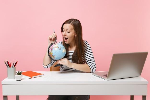 鉛筆で地球を指して、現代のpcラップトップで白い机に座って仕事をしながら休暇を計画している好奇心旺盛な女性