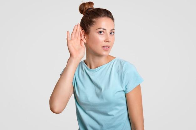 好奇心が強い女性は耳の近くに手を置いて、秘密の情報を盗聴または盗聴しようとします、うわさ話、白で分離されたカジュアルな青いtシャツを着たようです。大声で話しかけてあなたの声をもっと良くしてください