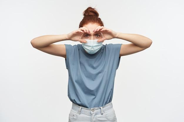 생강 머리를 가진 호기심 많은 여자가 롤빵에 모였습니다. 파란색 티셔츠와 안면 보호 마스크를 착용하십시오. 손으로 쌍안경을 모방하고 들여다보십시오. 흰 벽 위에 절연
