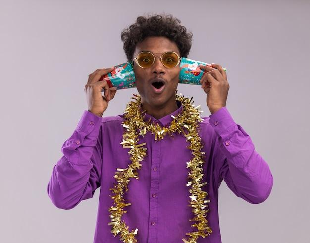 Curioso giovane afro-americano con gli occhiali con la ghirlanda di orpelli intorno al collo che tiene i bicchieri di plastica di natale accanto alle orecchie ascoltando la conversazione guardando la telecamera isolata su sfondo bianco