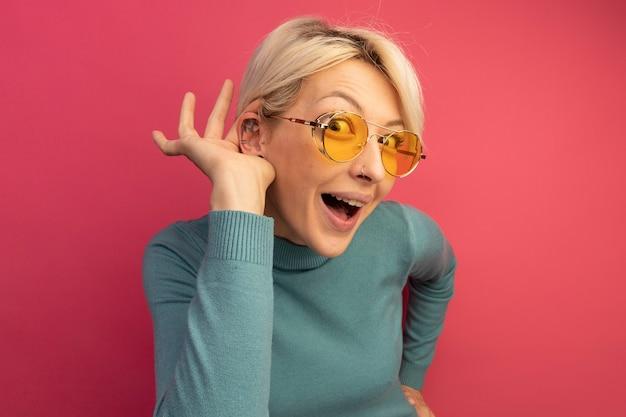 Curioso giovane ragazza bionda che indossa occhiali da sole tenendo la mano sulla vita facendo non riesco a sentirti gesto