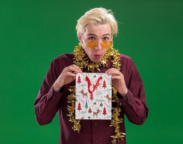 Любопытный молодой блондин в очках с гирляндой из мишуры на шее держит рождественский подарочный пакет, изолированный на зеленой стене