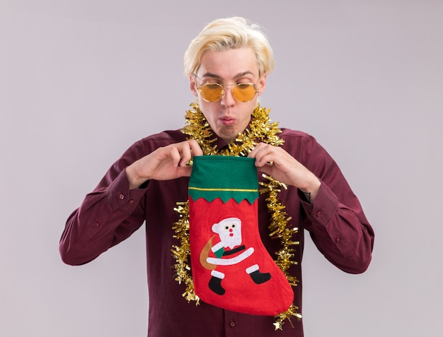 Curious young blonde man wearing glasses with tinsel garland around neck holding christmas stocking looking inside it isolated on white background