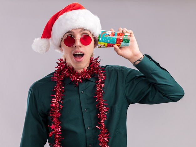 Curious young blonde man wearing santa hat and glasses with tinsel garland around neck holding plastic christmas cups next to ears listening to secrets looking at side isolated on white background
