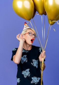 眼鏡をかけている好奇心旺盛な若いブロンドのパーティーの女性と側を見て風船を保持している誕生日の帽子は、紫色の壁に隔離されたジェスチャーを聞くことができません
