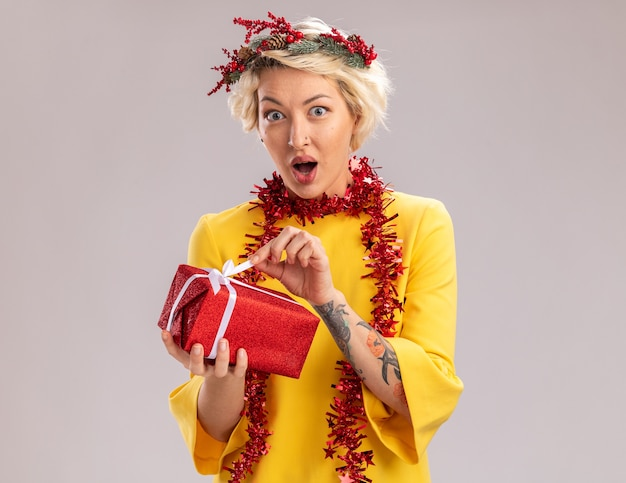 Curious young blonde woman wearing christmas head wreath and tinsel garland around neck holding christmas gift package looking  grabbing ribbon isolated on white wall with copy space