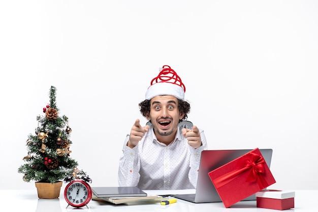 Curioso giovane imprenditore con buffo cappello di babbo natale interrogatorio su qualcosa in ufficio su sfondo bianco