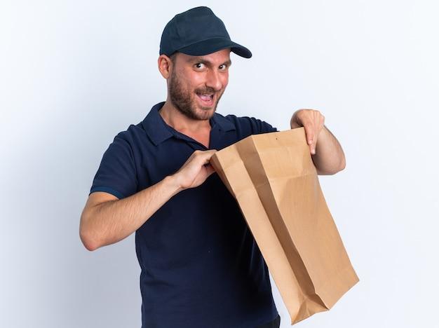 Curioso giovane fattorino caucasico in uniforme blu e pacchetto di carta che apre il cappuccio
