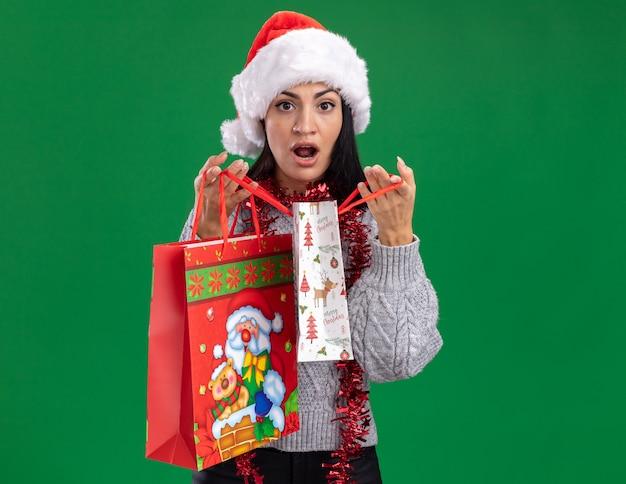 Curiosa giovane ragazza caucasica che indossa il cappello di natale e la ghirlanda di orpelli intorno al collo che tiene i sacchetti del regalo di natale che aprono uno isolato sulla parete verde con lo spazio della copia