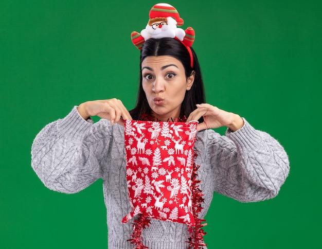 Любопытная молодая кавказская девушка в ободке санта-клауса и гирлянде из мишуры на шее держит мешок с рождественским подарком, открывая его, глядя в камеру, изолированную на зеленом фоне