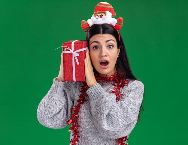 Любопытная молодая кавказская девушка в головной повязке санта-клауса и гирлянде из мишуры на шее держит подарочный пакет, трогая голову, глядя в камеру, изолированную на зеленом фоне