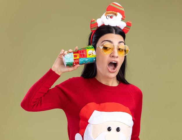 Curiosa giovane ragazza caucasica che indossa la fascia di babbo natale e un maglione con gli occhiali che tengono la tazza di natale in plastica accanto all'orecchio guardando il lato ascoltando la conversazione isolata sul muro verde oliva