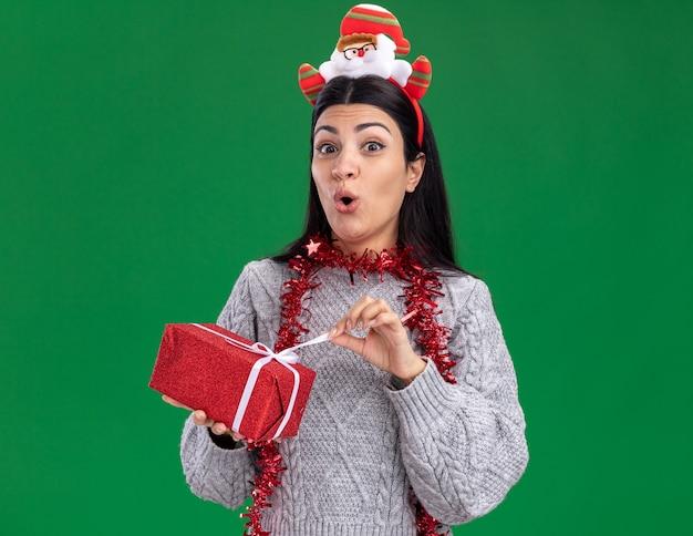 Curiosa giovane ragazza caucasica che indossa la fascia di babbo natale e la ghirlanda di orpelli intorno al collo che tiene il pacchetto regalo guardando la telecamera afferrando il nastro isolato su sfondo verde