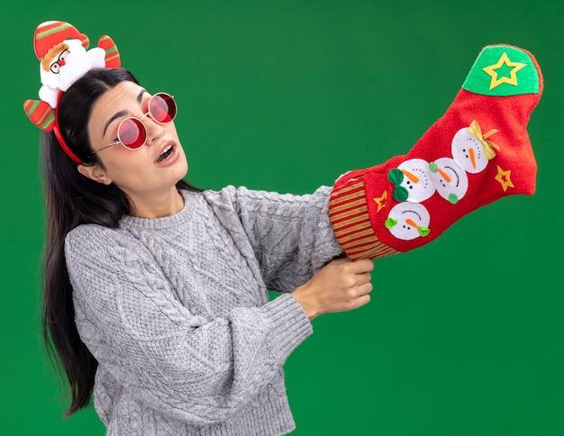 Любопытная молодая кавказская девушка в головной повязке санта-клауса в очках держит рождественский чулок, глядя на него, кладя руку внутрь, изолированную на зеленом фоне