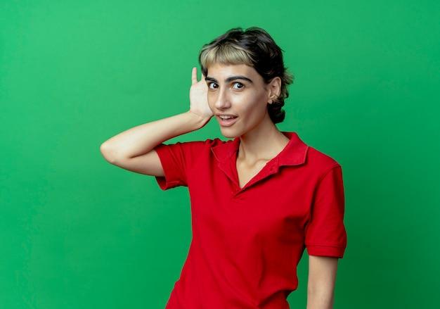 Любопытная молодая кавказская девушка со стрижкой пикси не слышит вашего жеста, изолированного на зеленом фоне с копией пространства