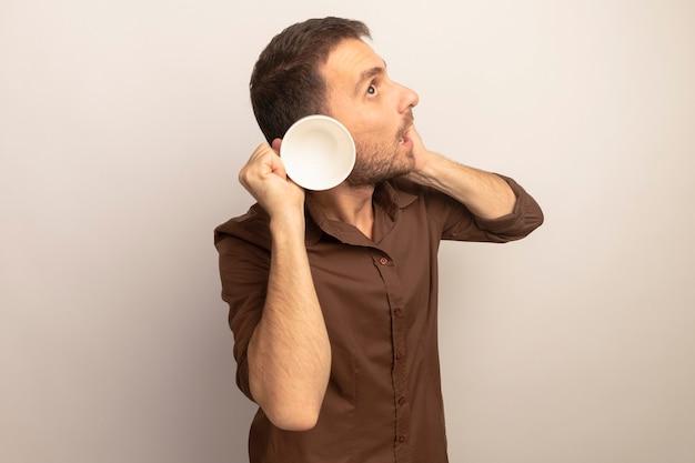 Curioso giovane uomo caucasico mettendo la mano sul viso toccando l'orecchio con la tazza alzando lo sguardo isolato su sfondo bianco con spazio di copia
