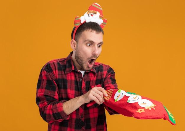 Любопытный молодой кавказский мужчина в головной повязке санта-клауса держит и смотрит на рождественский чулок, кладя руку внутрь, изолированную на оранжевом фоне