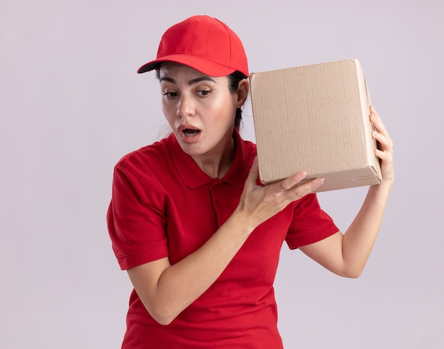 Curiosa giovane donna delle consegne in uniforme e cappuccio che tiene una scatola di cartone vicino all'orecchio guardando in basso ascoltando