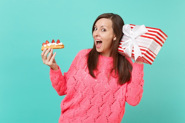 ニットのピンクのセーターを着た好奇心旺盛な少女は、エクレアケーキ、青い背景に分離されたギフトリボン付きの赤い縞模様のプレゼントボックスを保持します。バレンタインの女性の日の誕生日の休日の概念。コピースペースをモックアップします。