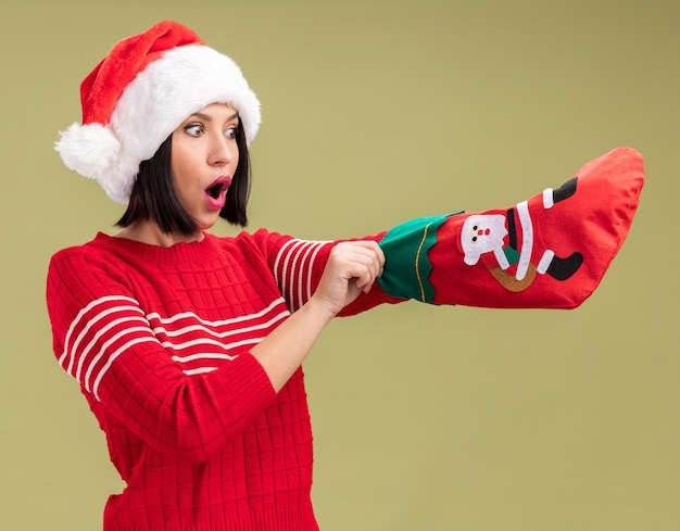 Любопытная молодая девушка в шляпе санта-клауса держит рождественский чулок, глядя на него, кладя руку внутрь, изолированную на оливково-зеленом фоне