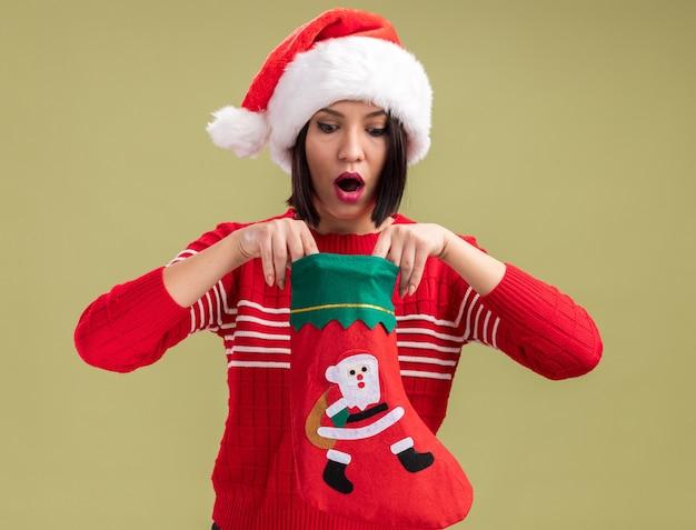 Любопытная молодая девушка в шляпе санта-клауса держит рождественский чулок, глядя внутрь него на оливково-зеленом фоне