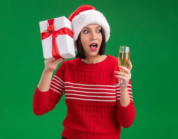 Любопытная молодая девушка в шляпе санта-клауса держит подарочный пакет возле головы и бокал шампанского, глядя в сторону, изолированную на зеленом фоне