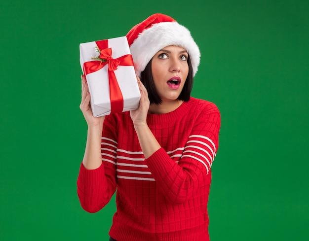 Любопытная молодая девушка в шляпе санта-клауса держит подарочный пакет возле головы, глядя вверх, слушая изолированную на зеленой стене с копией пространства