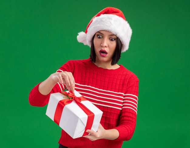 Curious young girl wearing santa hat holding and looking at gift package grabbing ribbon isolated on green wall