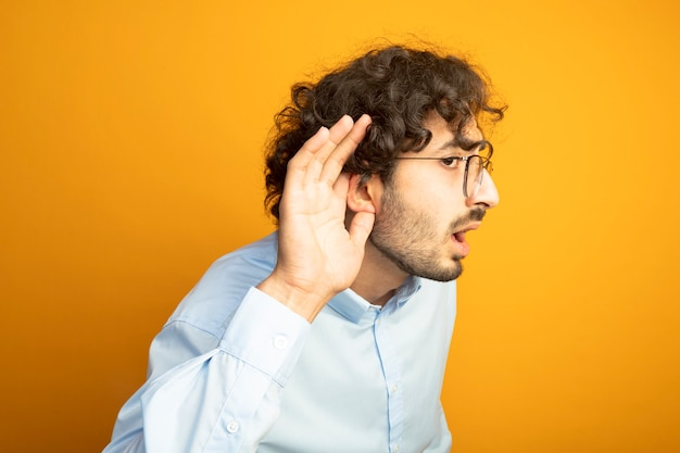 Curious young handsome caucasian man wearing glasses looking straight keeping hand near ear doing i can't hear you gesture isolated on orange background with copy space