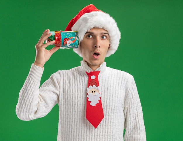 Curious young handsome guy wearing christmas hat and santa claus tie holding plastic christmas cup next to ear looking at side listening to conversation isolated on green background