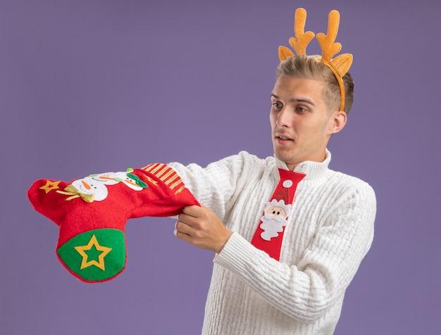 Любопытный молодой красивый парень в повязке на голову из оленьих рогов и галстуке санта-клауса держит и смотрит на рождественский чулок, кладя руку внутрь, изолированную на фиолетовом фоне