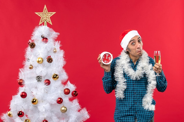 Curious young man with santa claus hat and holding a glass of wine and clock standing near christmas tree