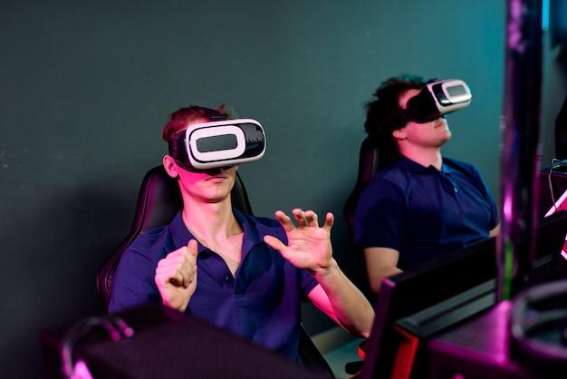 어두운 e- 스포츠 클럽에 앉아서 네트워크 비디오 게임을하는 동안 가상 현실 시뮬레이터를 사용하는 같은 티셔츠를 입은 호기심 많은 젊은이