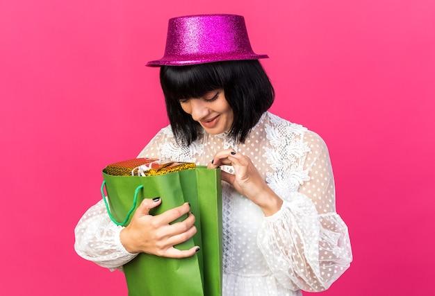Una ragazza curiosa che indossa un cappello da festa tiene in mano un pacchetto regalo in un sacchetto di carta che guarda all'interno del sacchetto di carta isolato su una parete rosa
