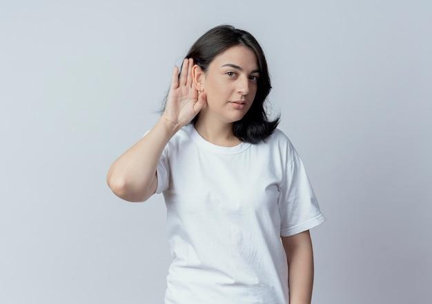 Любопытная молодая симпатичная кавказская девушка не слышит, как вы жестикулируете на камеру, изолированную на белом фоне с копией пространства