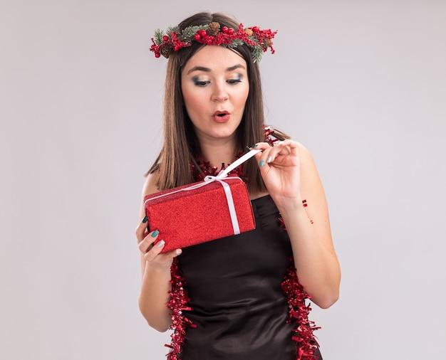 Curiosa giovane bella ragazza caucasica che indossa ghirlanda di testa di natale e ghirlanda di orpelli intorno al collo tenendo e guardando il pacchetto regalo che afferra il nastro isolato su sfondo bianco con lo spazio della copia
