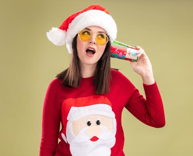 대화를 듣고 귀 옆에 플라스틱 크리스마스 컵을 들고 안경 산타 클로스 스웨터와 모자를 쓰고 호기심 어린 예쁜 백인 여자
