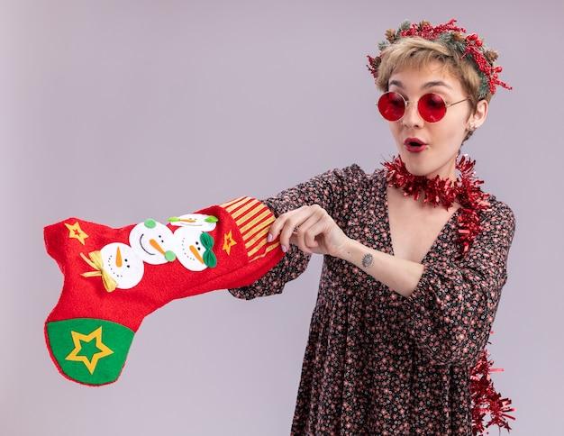 Любопытная молодая красивая девушка в рождественском венке и гирлянде из мишуры на шее в очках с рождественским чулком, глядя на него, кладя руку внутрь, изолированную на белом фоне