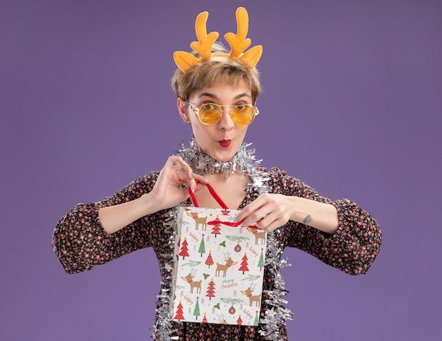 크리스마스 선물 가방을 들고 안경 목 주위에 순록 뿔 머리띠와 반짝이 갈 랜드를 입고 호기심 어린 예쁜 여자가 보라색 배경에 고립 된 카메라를보고 열어