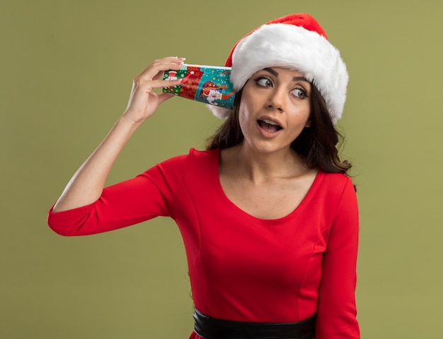 Curious young pretty girl wearing santa hat holding christmas coffee cup next to ear listening to conversation looking at side
