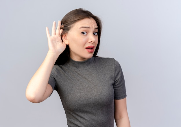 Curious young pretty woman doing can't hear you gesture at camera isolated on white background with copy space