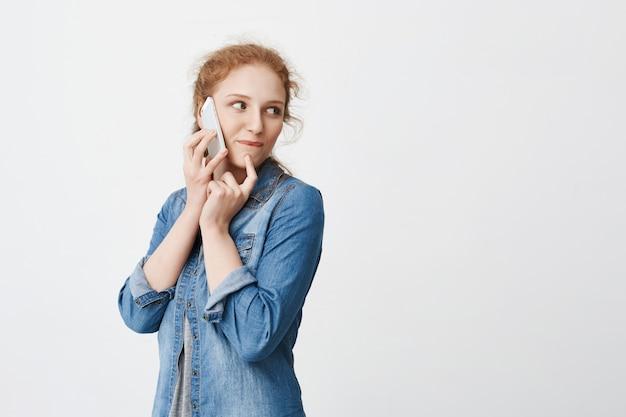 好奇心旺盛な若い赤毛の女の子がスマートフォンで話しながら右を向いて、何かを望んでいるかのように唇の近くに手を握って