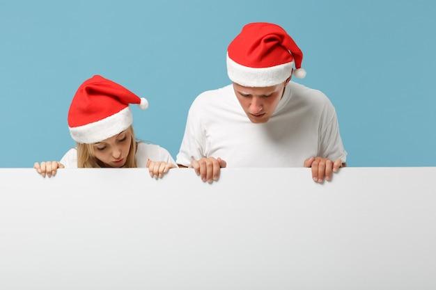 クリスマスの帽子の好奇心が強い若いサンタカップルの友人の男と女