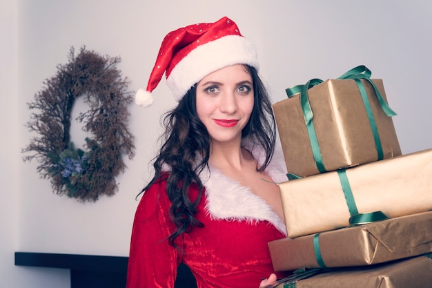 Curious young santa girl, christmas hat holding box with gift present on grey wall background. happy new year celebration holiday party concept.