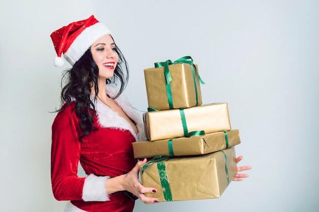好奇心が強い若いサンタの女の子、灰色の壁の背景にプレゼントプレゼントとボックスを保持しているクリスマス帽子。明けましておめでとうございますお祝いホリデーパーティーのコンセプト。コピースペースをモックアップします。うれしそうなサンタ