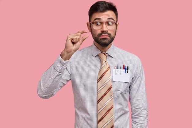 Curioso giovane regista maschio con la barba lunga mostra un piccolo oggetto, vestito con abiti formali, gesticola con la mano