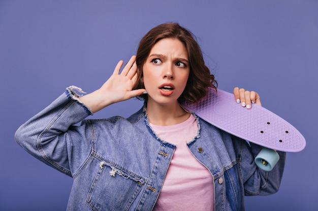 Любопытная молодая женщина в прослушивании джинсовой куртки. очаровательная кудрявая девушка позирует.