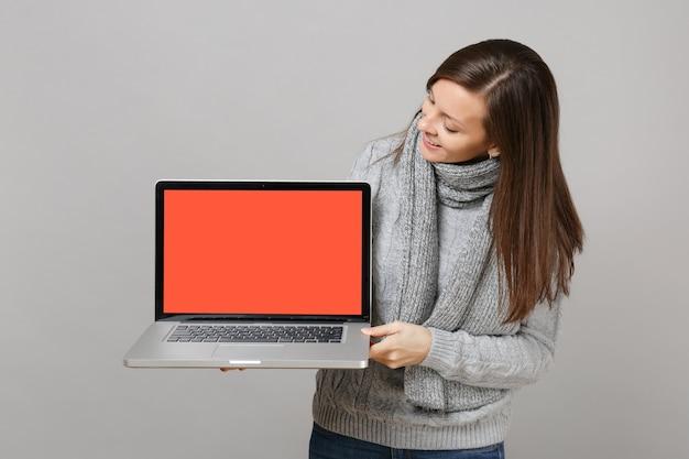 灰色のセーターを着た好奇心旺盛な若い女性、スカーフは灰色の背景で隔離の空白の空の画面でラップトップpcコンピューターを探しています。健康的なライフスタイル、オンライン治療コンサルティング、寒い季節のコンセプト。