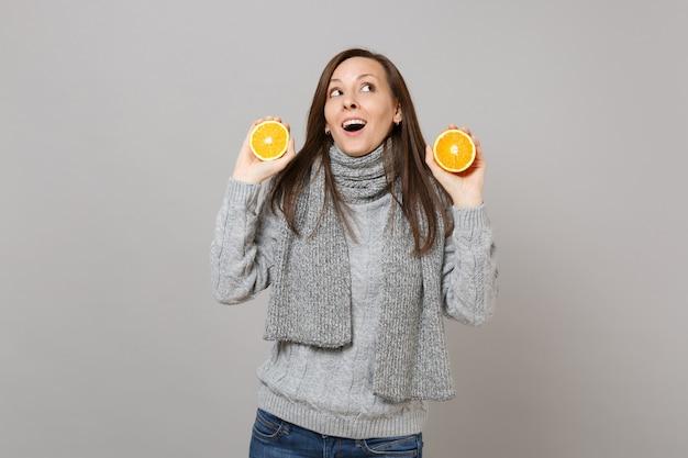 Любопытная молодая женщина в сером свитере, шарфе смотрит вверх и держит апельсины, изолированные на сером стенном фоне. здоровый образ жизни моды, искренние эмоции людей, концепция холодного сезона. копируйте пространство для копирования.